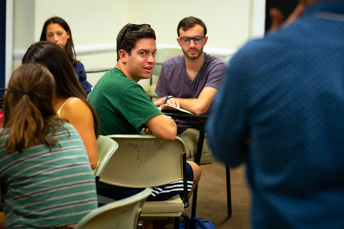 Student talking during a group discussion in a classroom.