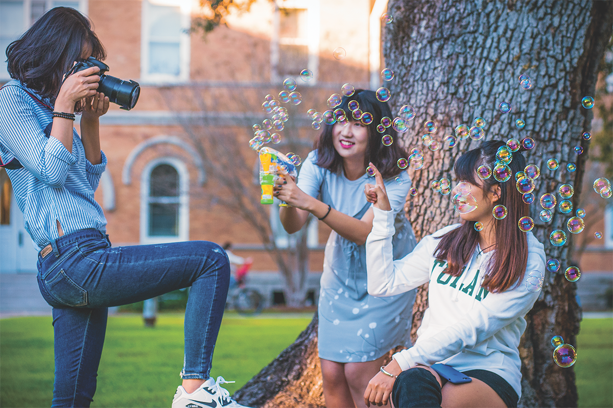 Two students playing with a bubble gun in the quad with a third person taking photos.