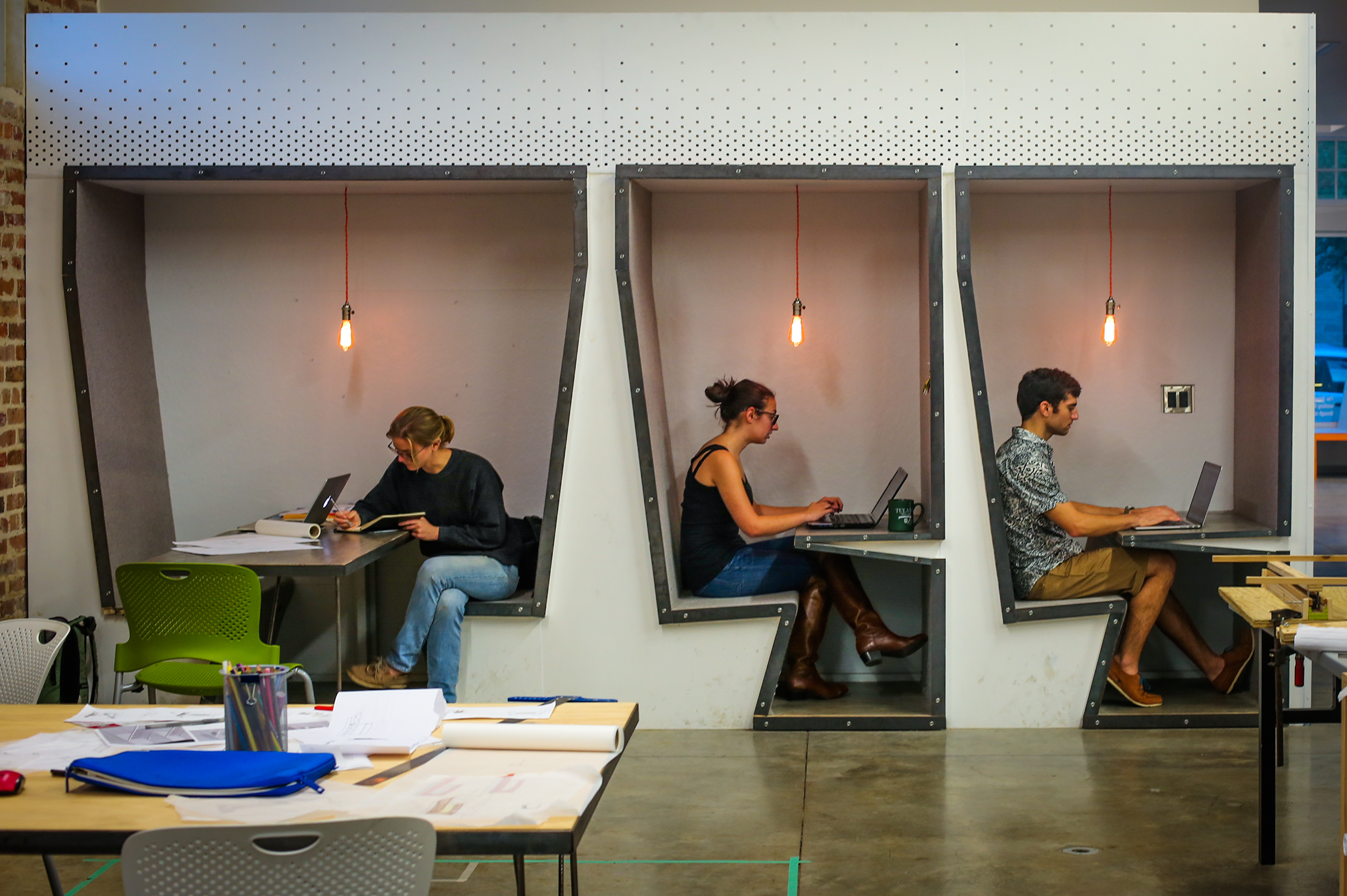 Three students studying in three booths.