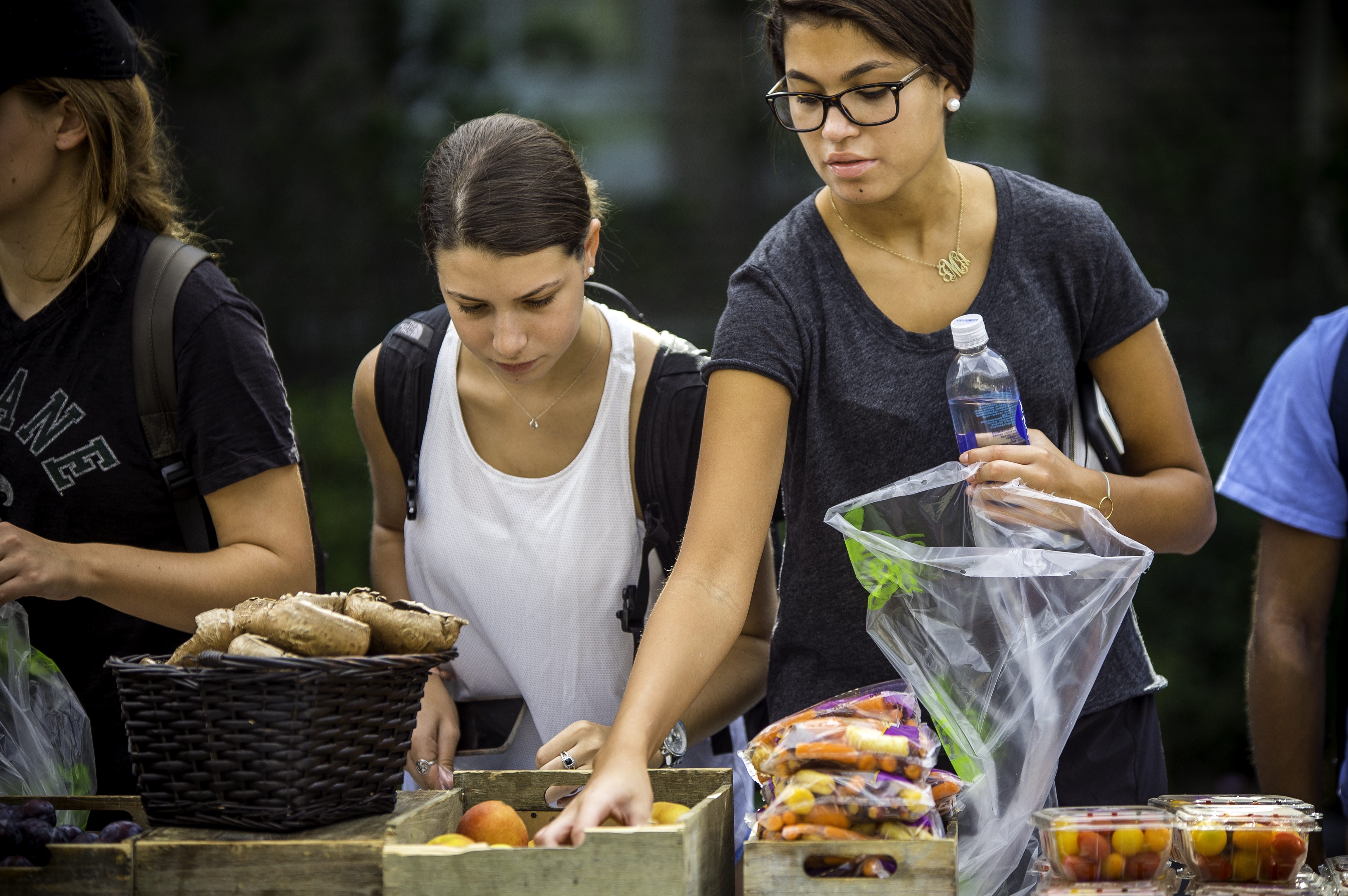 Two students shopping at the campus farmers market.