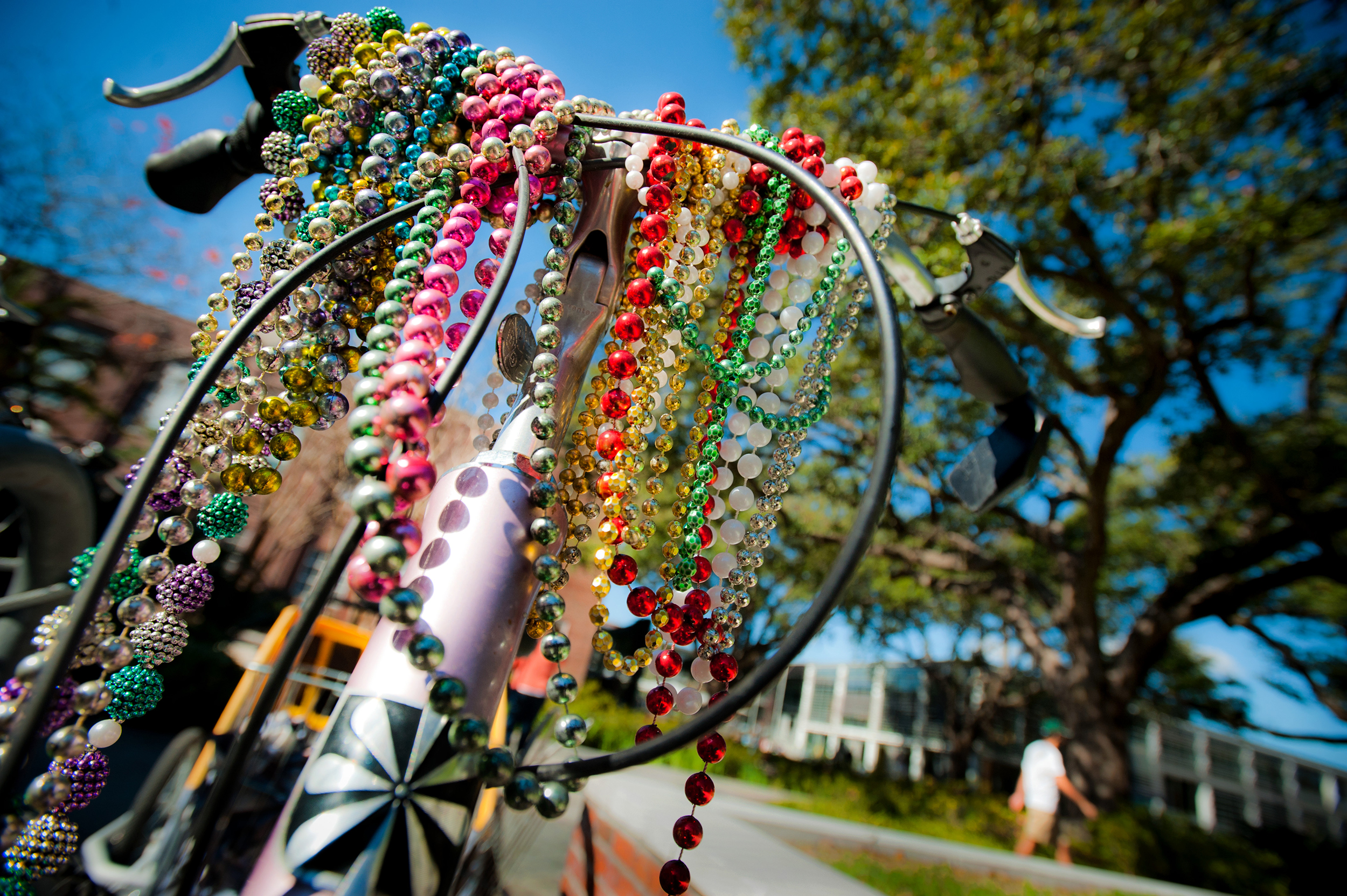 Mardi Gras beads dangling off front bicycle handle.