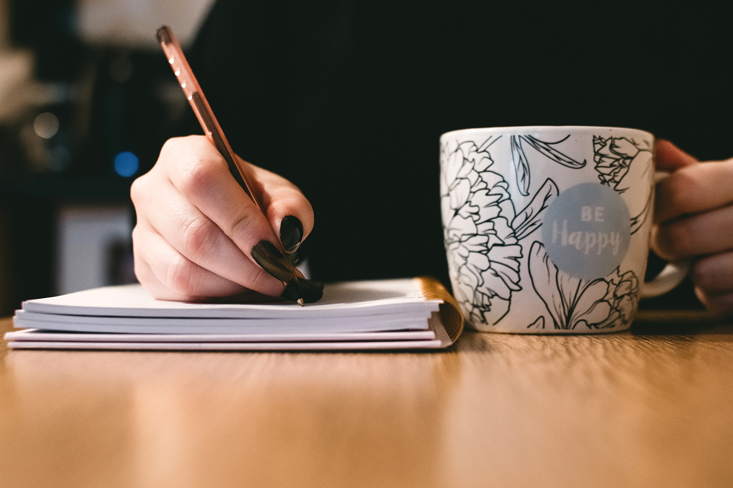One hand writes in notebook while the other holds a coffee mug.