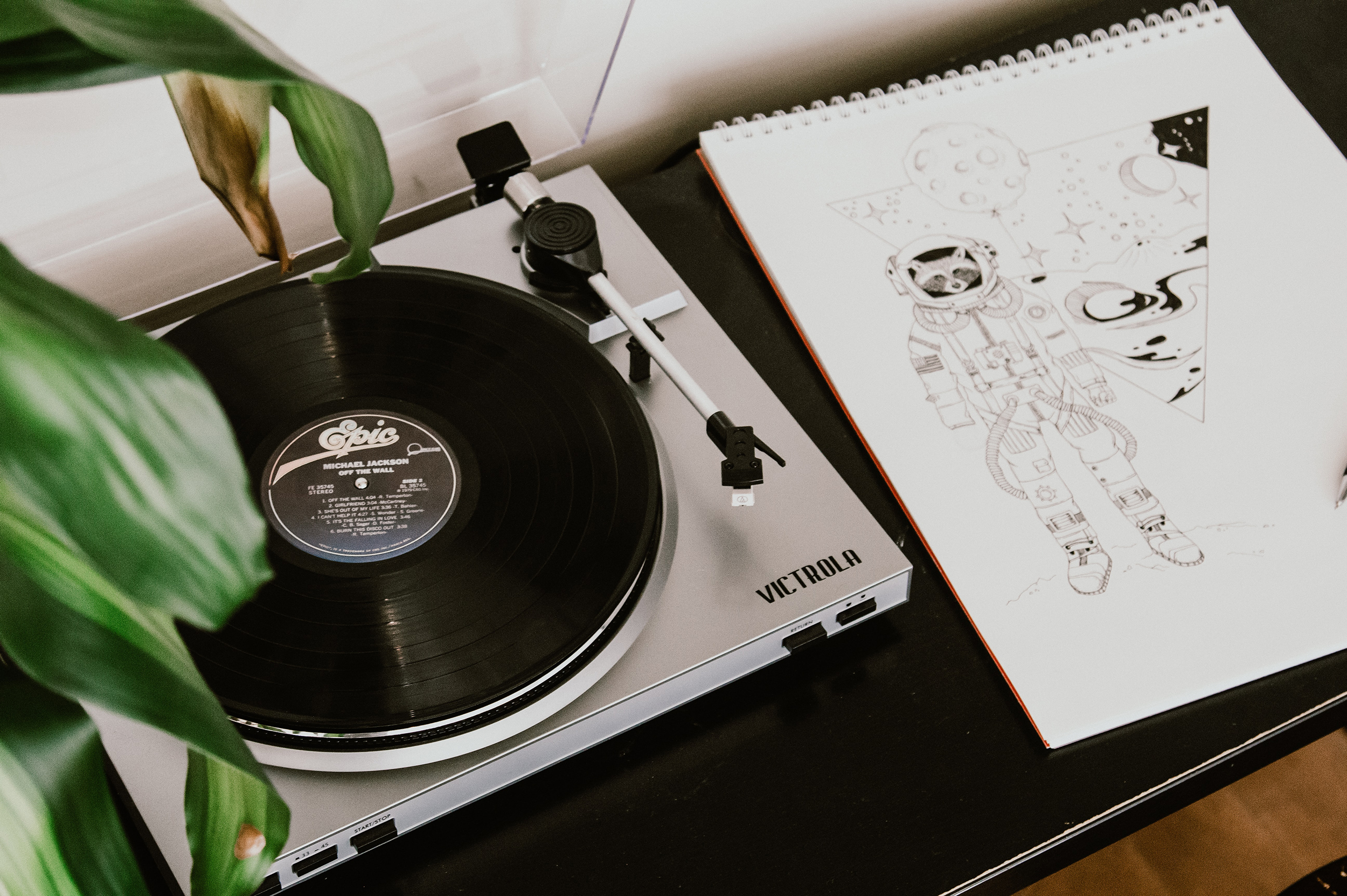 Record player next to a sketch pad.