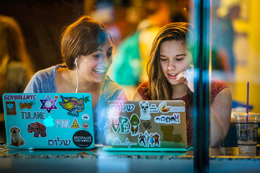 Two female students at the PJ's Coffee on Willow with their laptops open.
